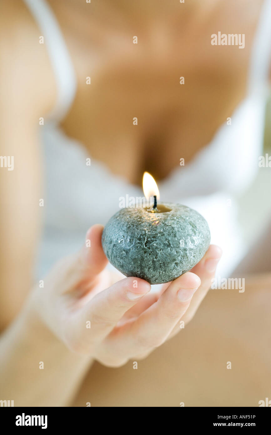 Woman holding up candle, cropped - Stock Image