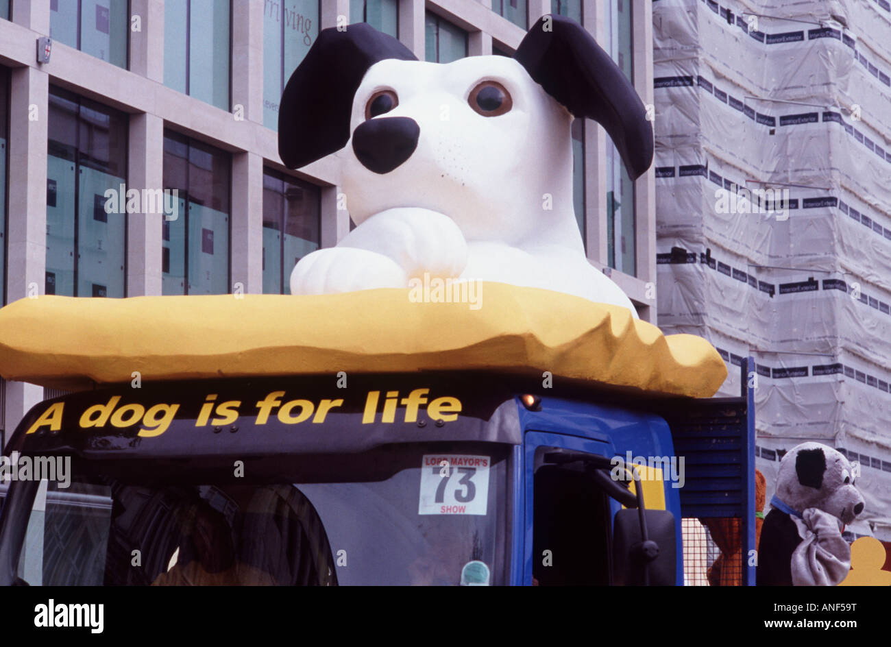 A dog is for life: Large black and white puppy with crossed paws on a dog rescue float, Lord Mayor's Show, City - Stock Image