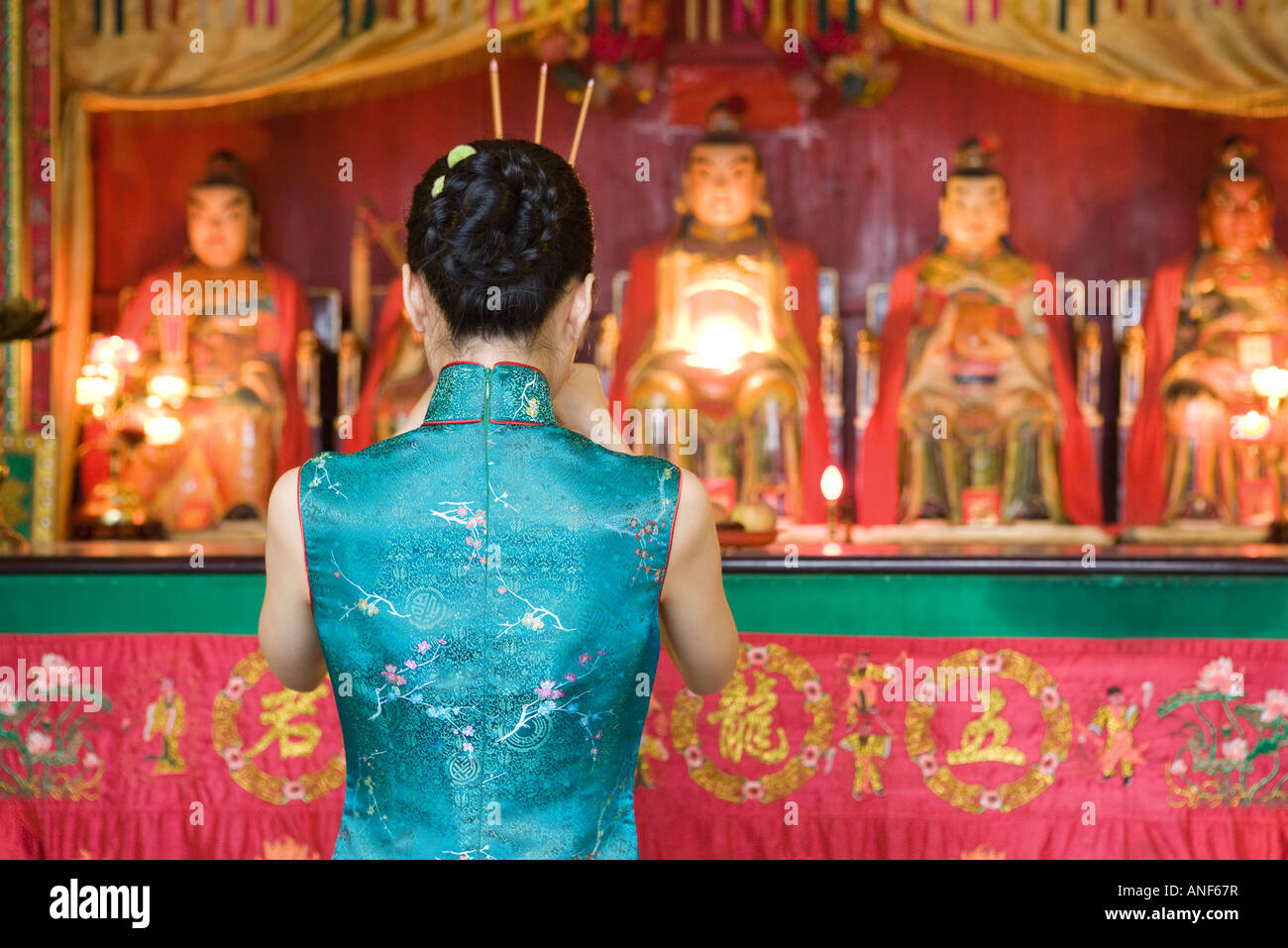 Young woman dressed in traditional Chinese clothing standing at shrine, rear view - Stock Image