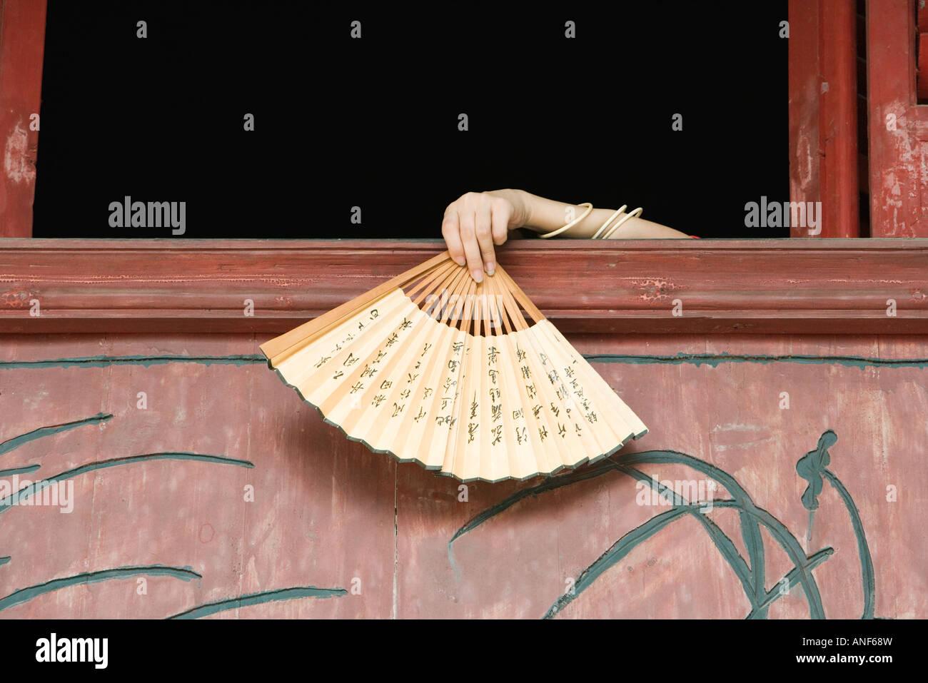Woman's hand holding fan over edge of windowsill - Stock Image