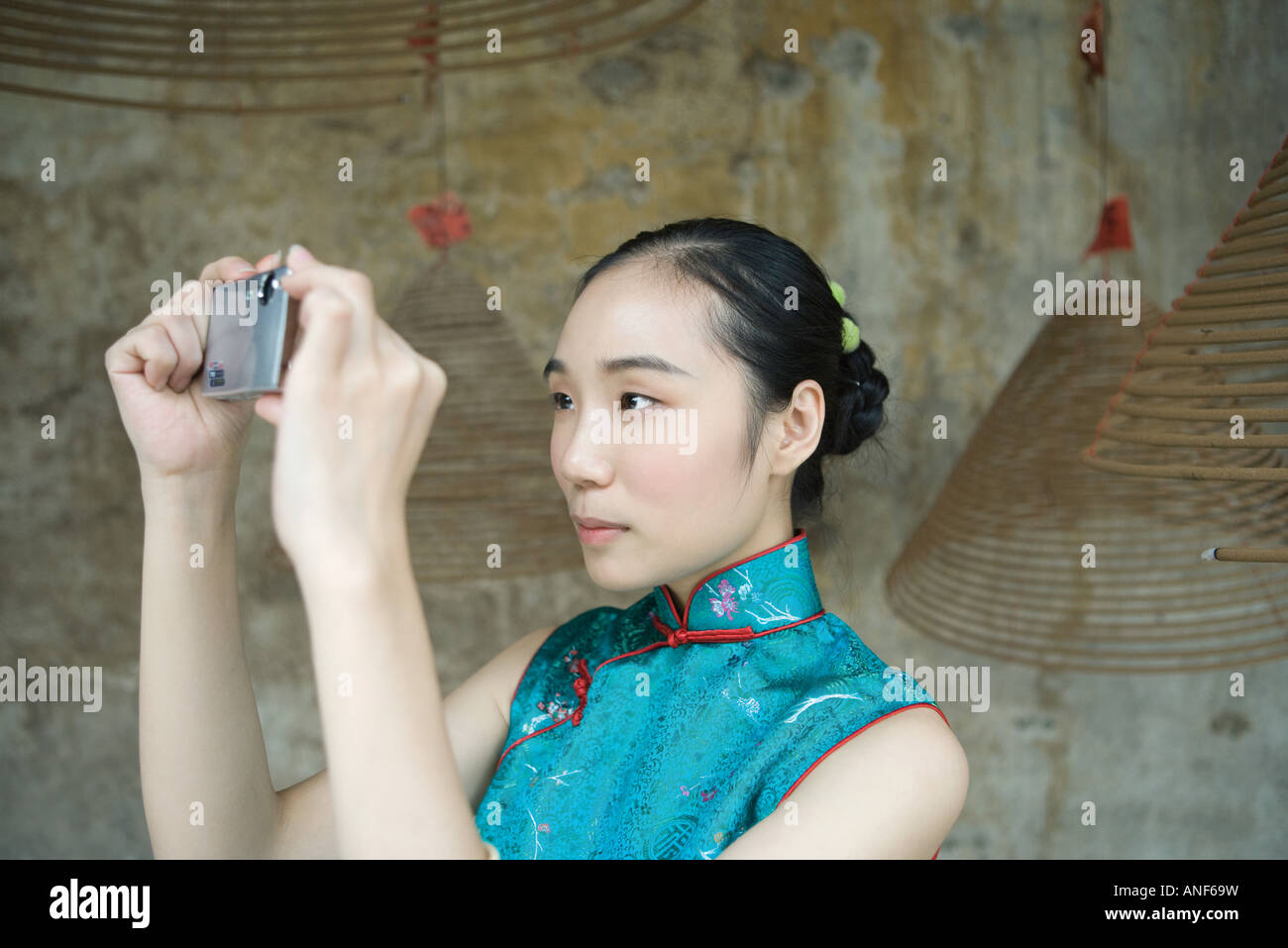 Young woman dressed in traditional Chinese clothing taking photo with digital camera - Stock Image