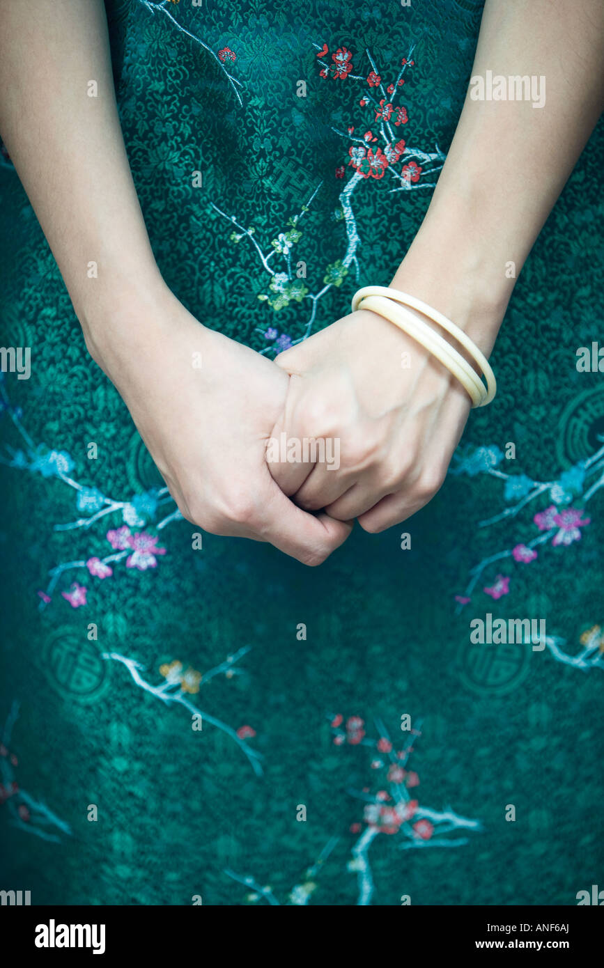 Young woman dressed in traditional Chinese clothing, hands clasped, close-up, cropped view - Stock Image