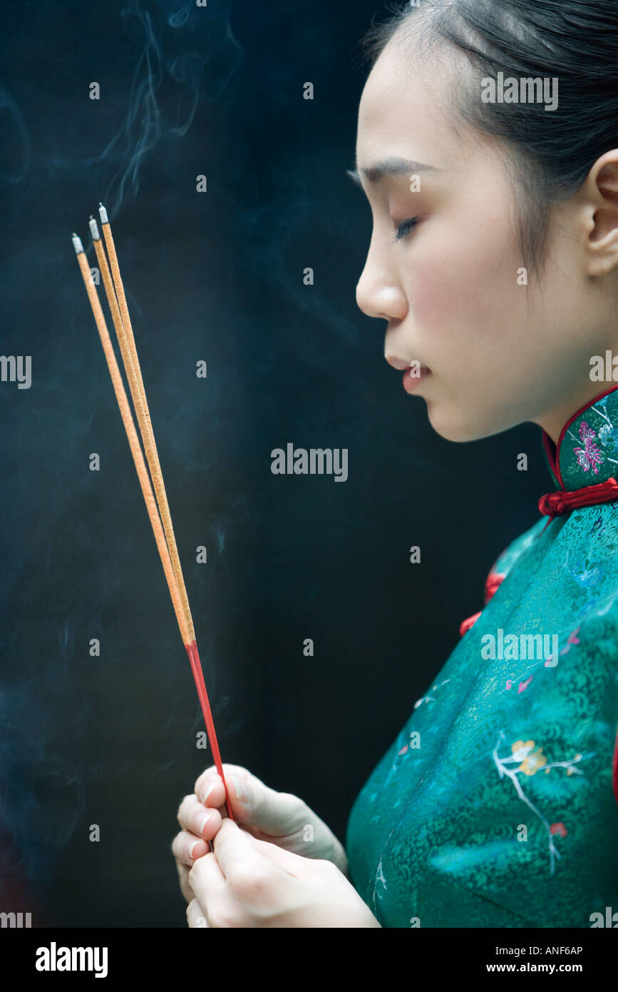 Young woman dressed in traditional Chinese clothing holding sticks of incense, eyes closed - Stock Image