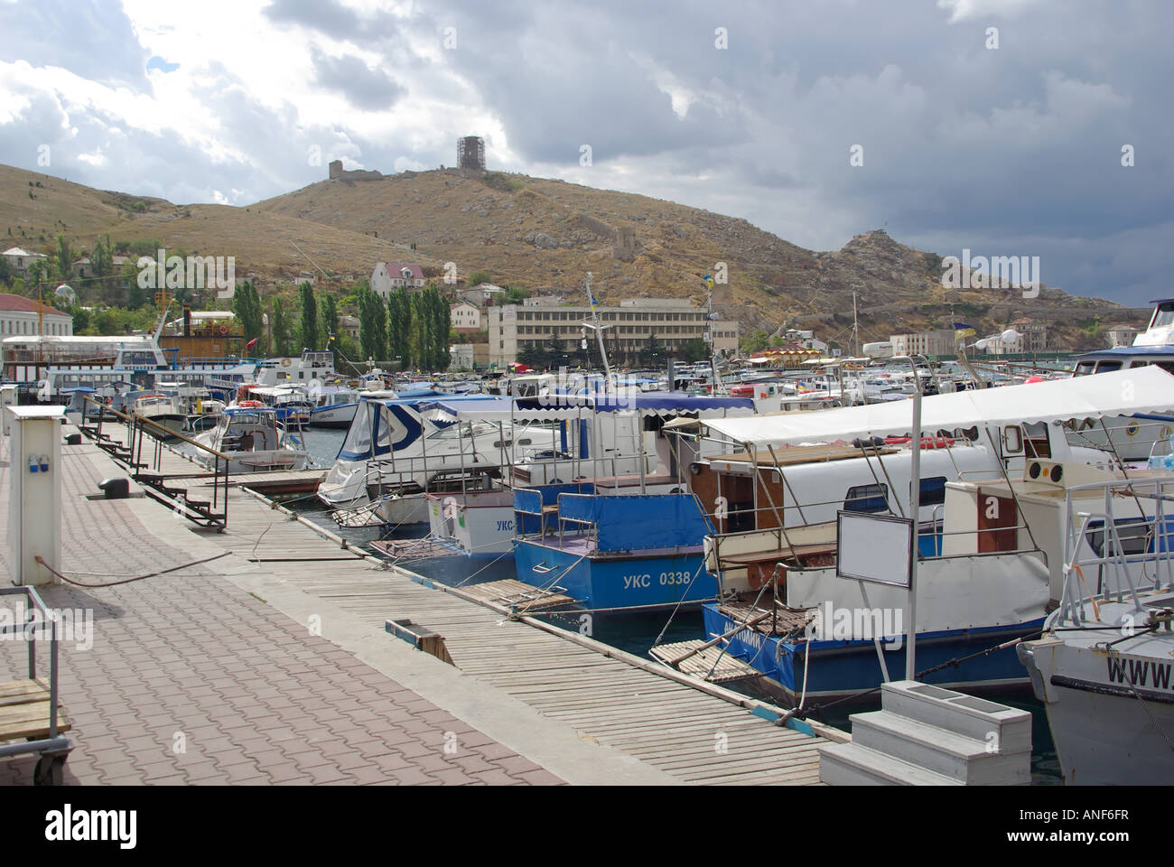 Balaclava bay harbour one time soviet nuclear submarine base motor boats beside promenade hillside and Genoese fort - Stock Image