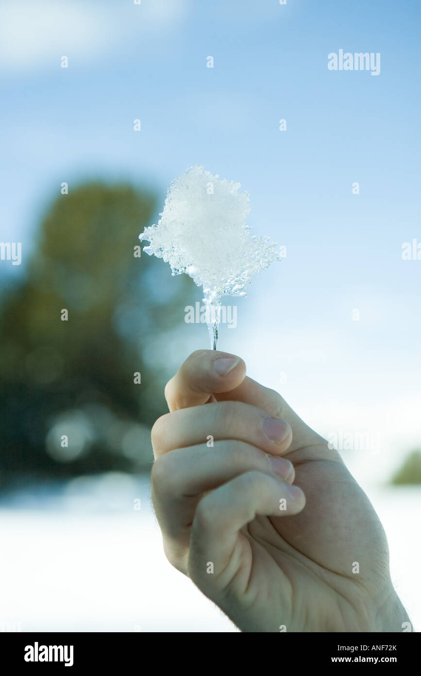 Hand holding up piece of ice - Stock Image