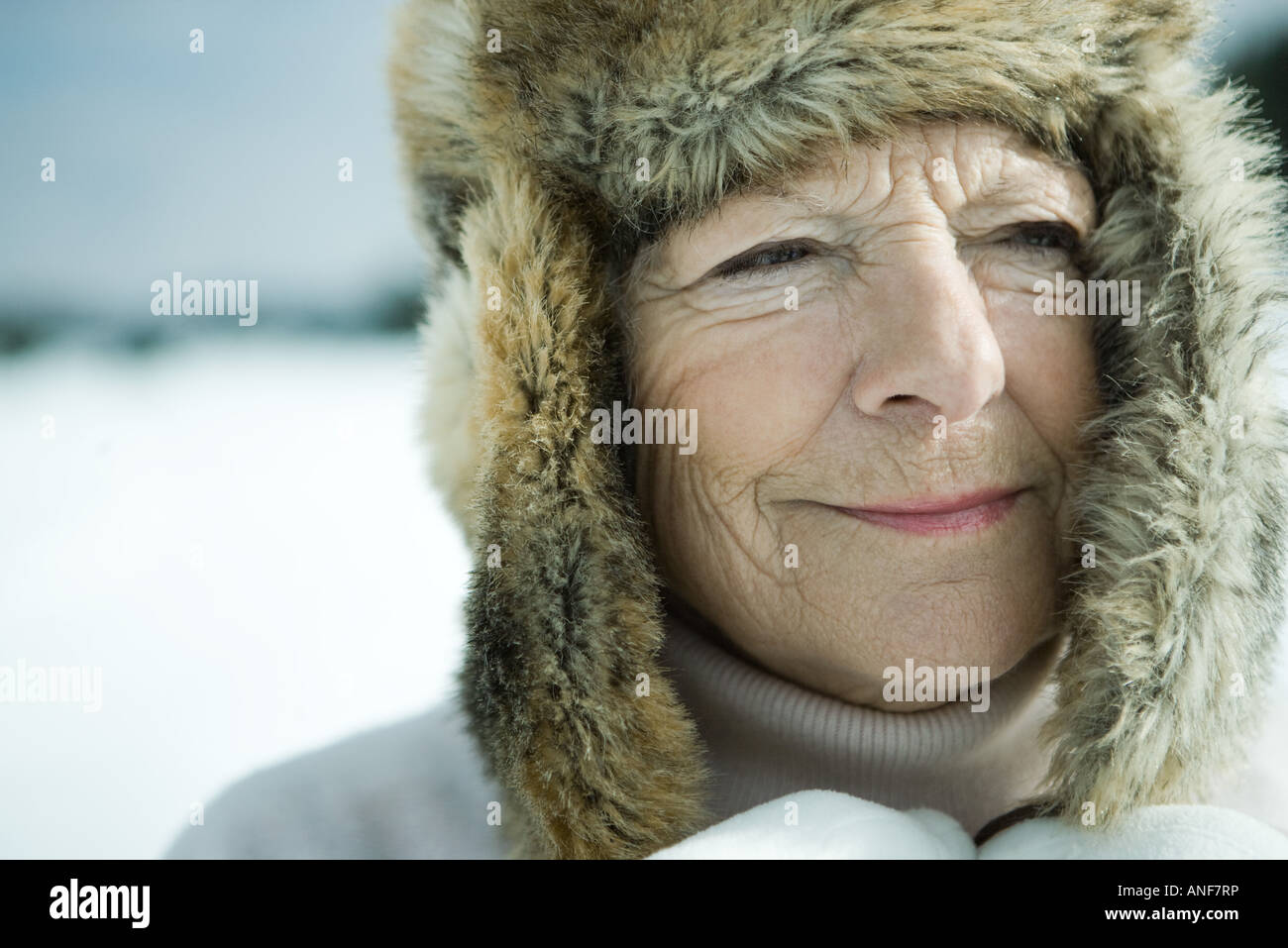 Senior woman standing in snowy landscape, head and shoulders - Stock Image