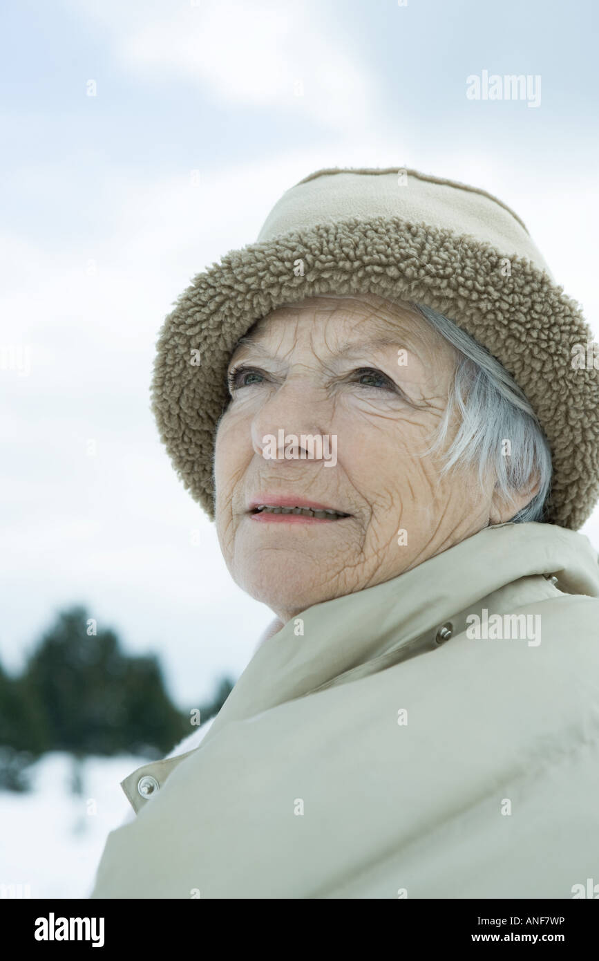 Senior woman in snowy landscape, head and shoulders, portrait - Stock Image