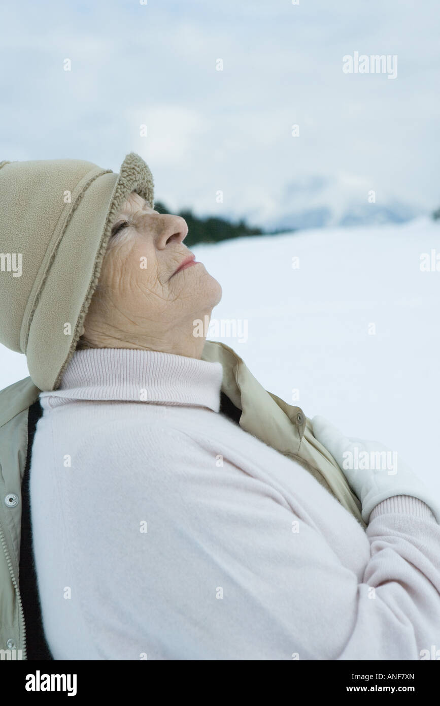 Senior woman standing in snowy landscape, looking up, waist up - Stock Image