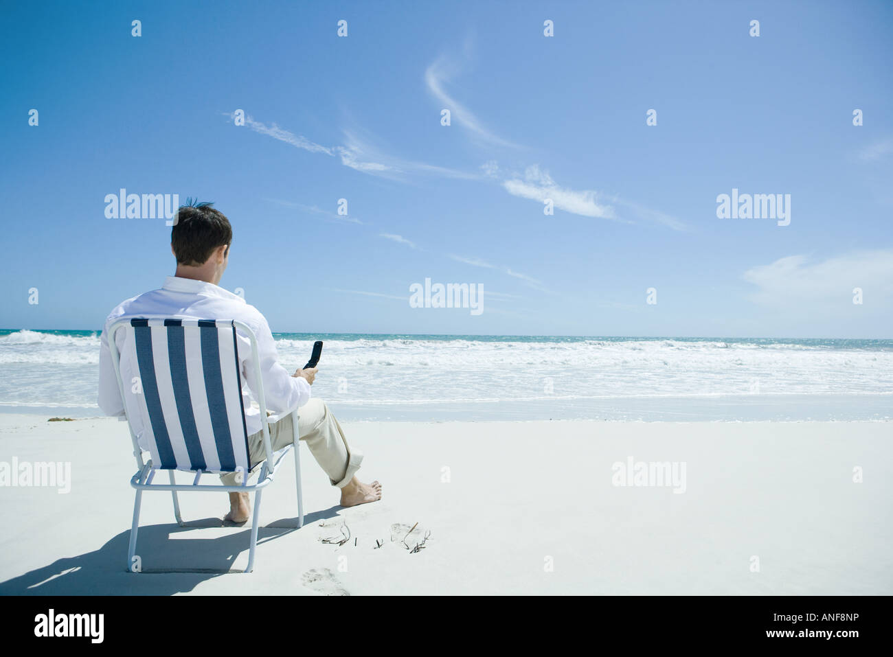 Man Sitting In Folding Chair On Beach Holding Cell Phone Rear View Stock Photo Alamy
