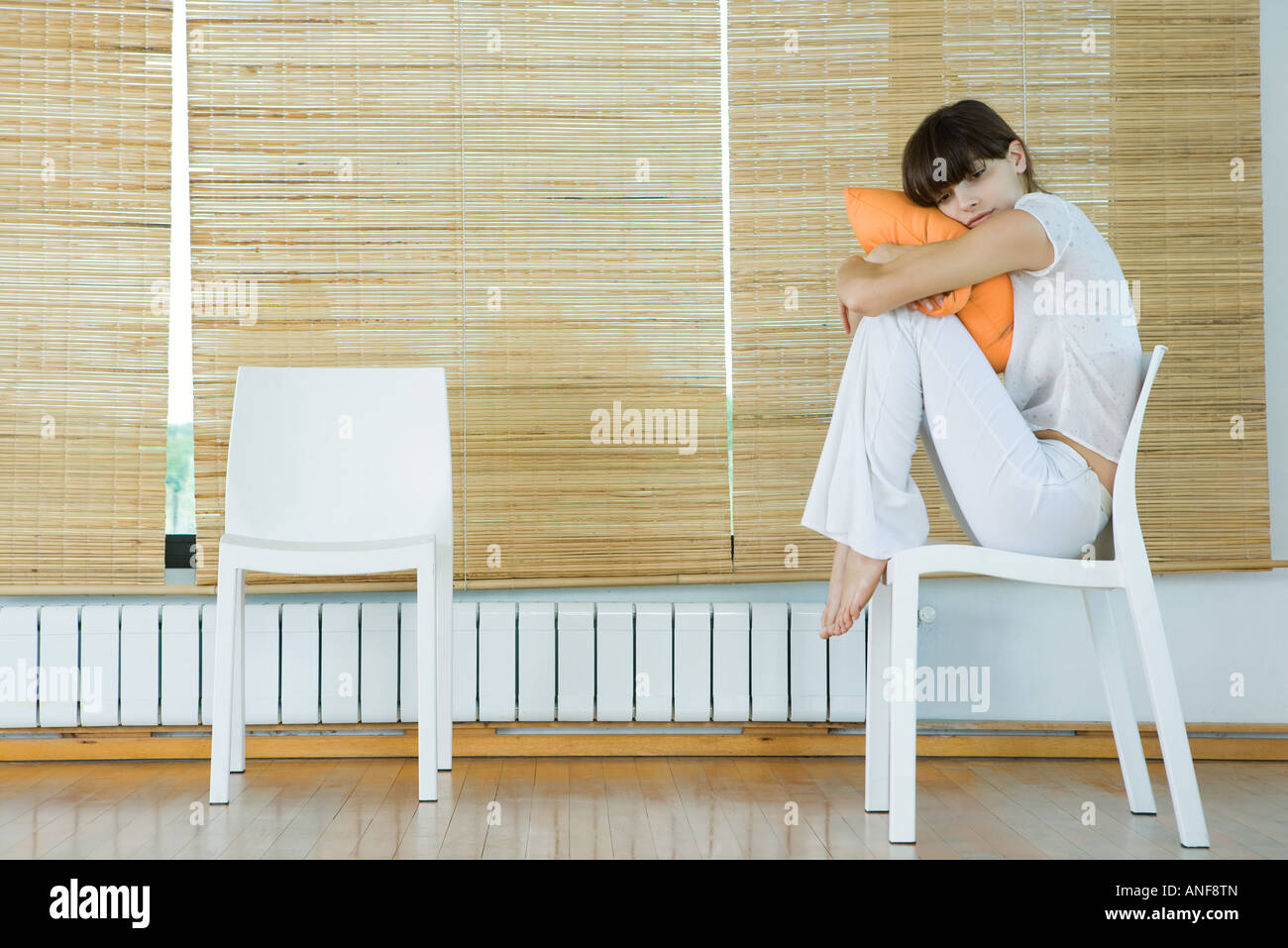 Young woman sitting in chair, hugging cushion - Stock Image