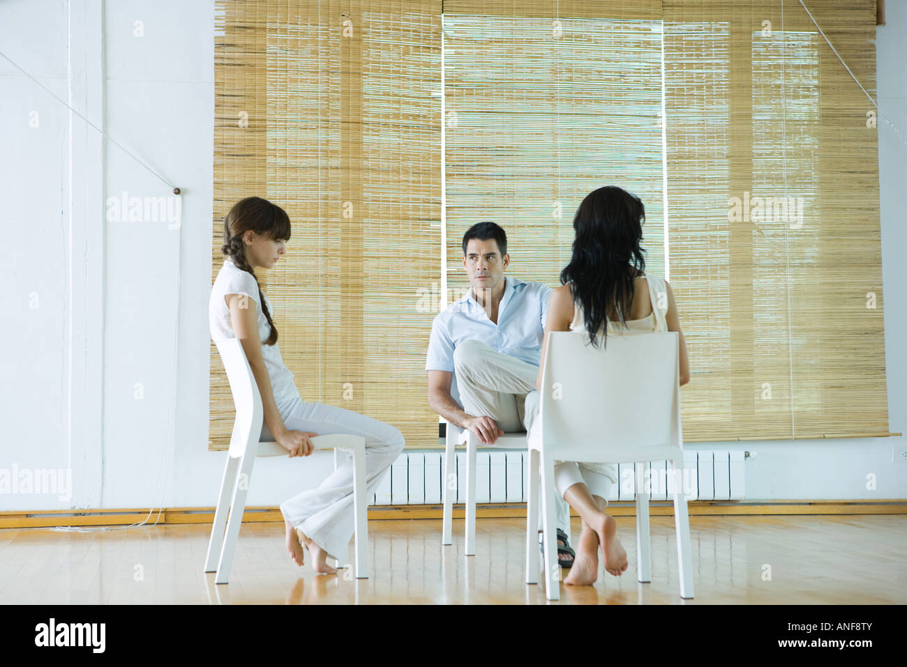 Three adults sitting in chairs, having therapy session, looking serious - Stock Image