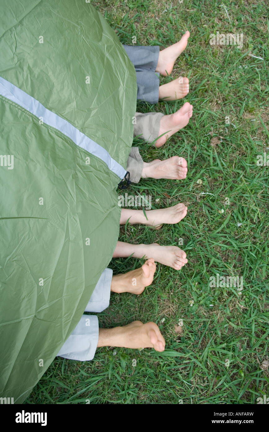 Young friends in tent, feet sticking out, high angle view - Stock Image