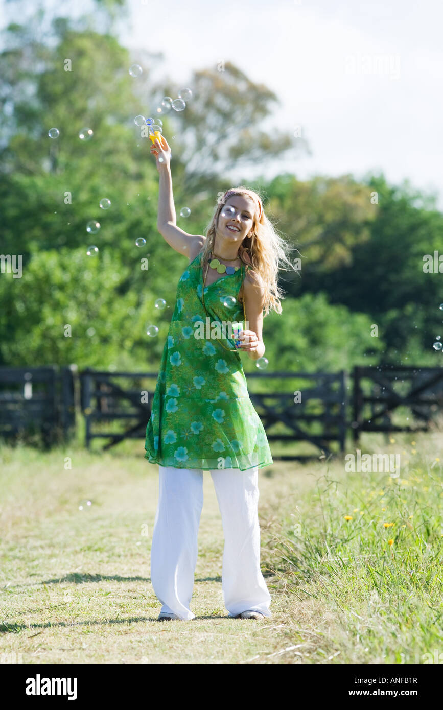 Young woman blowing bubbles in rural field, smiling at camera - Stock Image