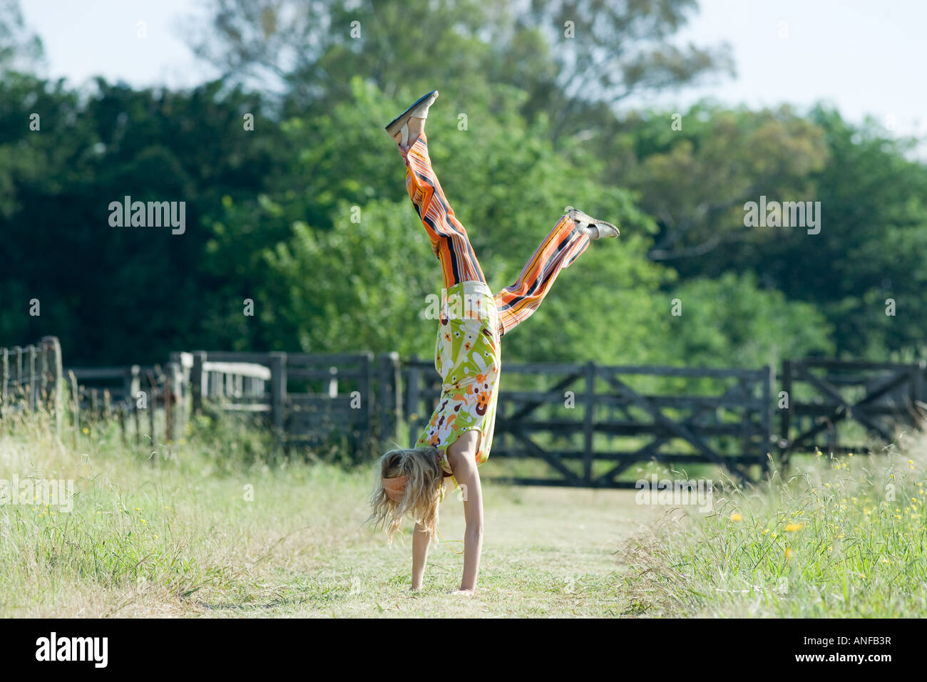 Young woman doing handstand in rural field - Stock Image