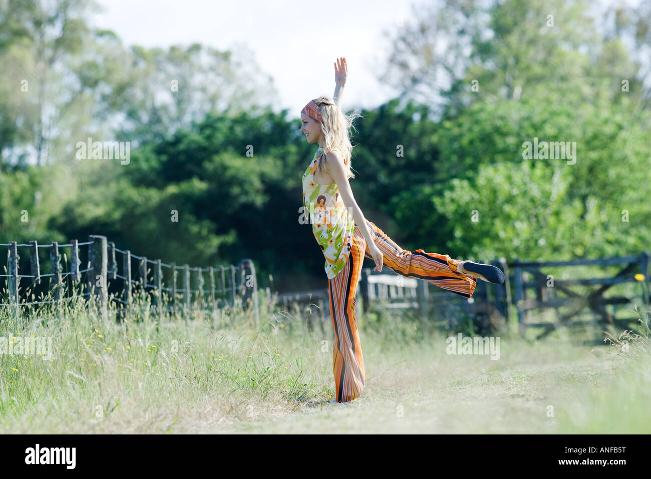 Young woman standing on one leg in rural field with arm raised - Stock Image
