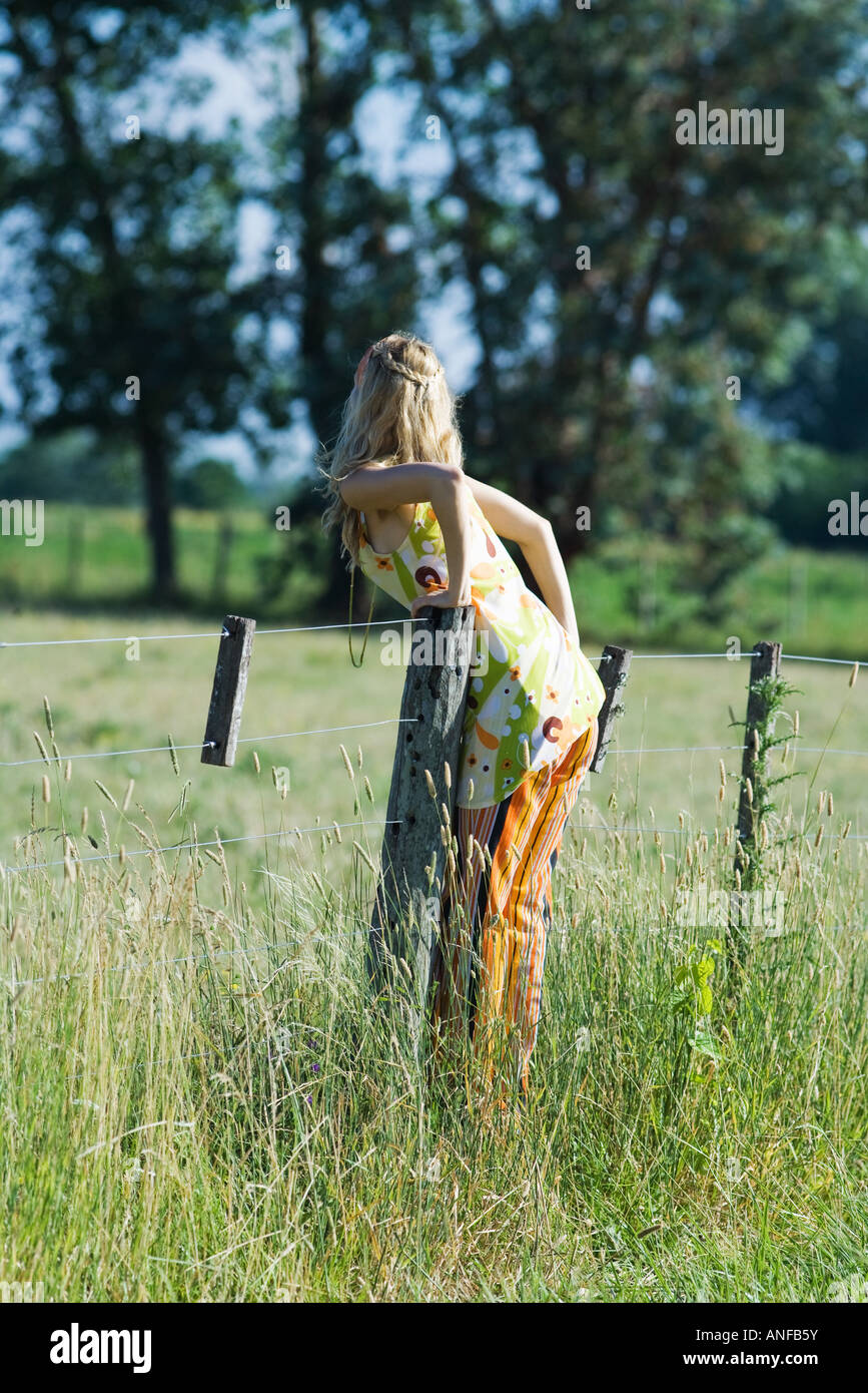 Young woman leaning over rural fence, rear view - Stock Image