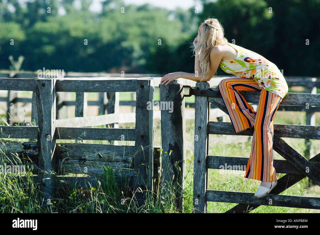 Young woman sitting on top of wooden fence, leaning on elbow, looking away - Stock Image