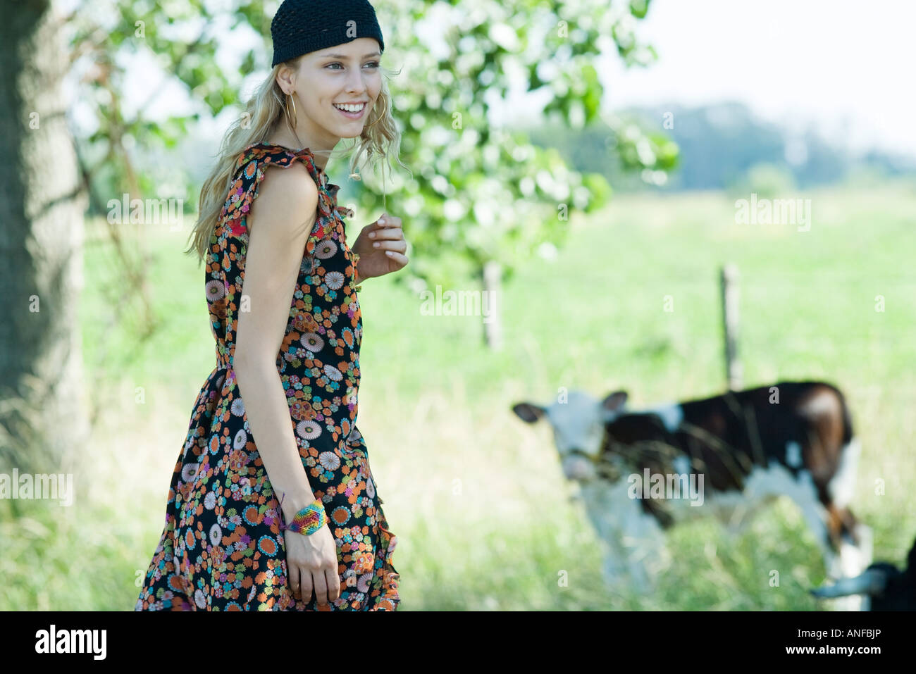 Young woman walking toward cow, smiling, looking away - Stock Image