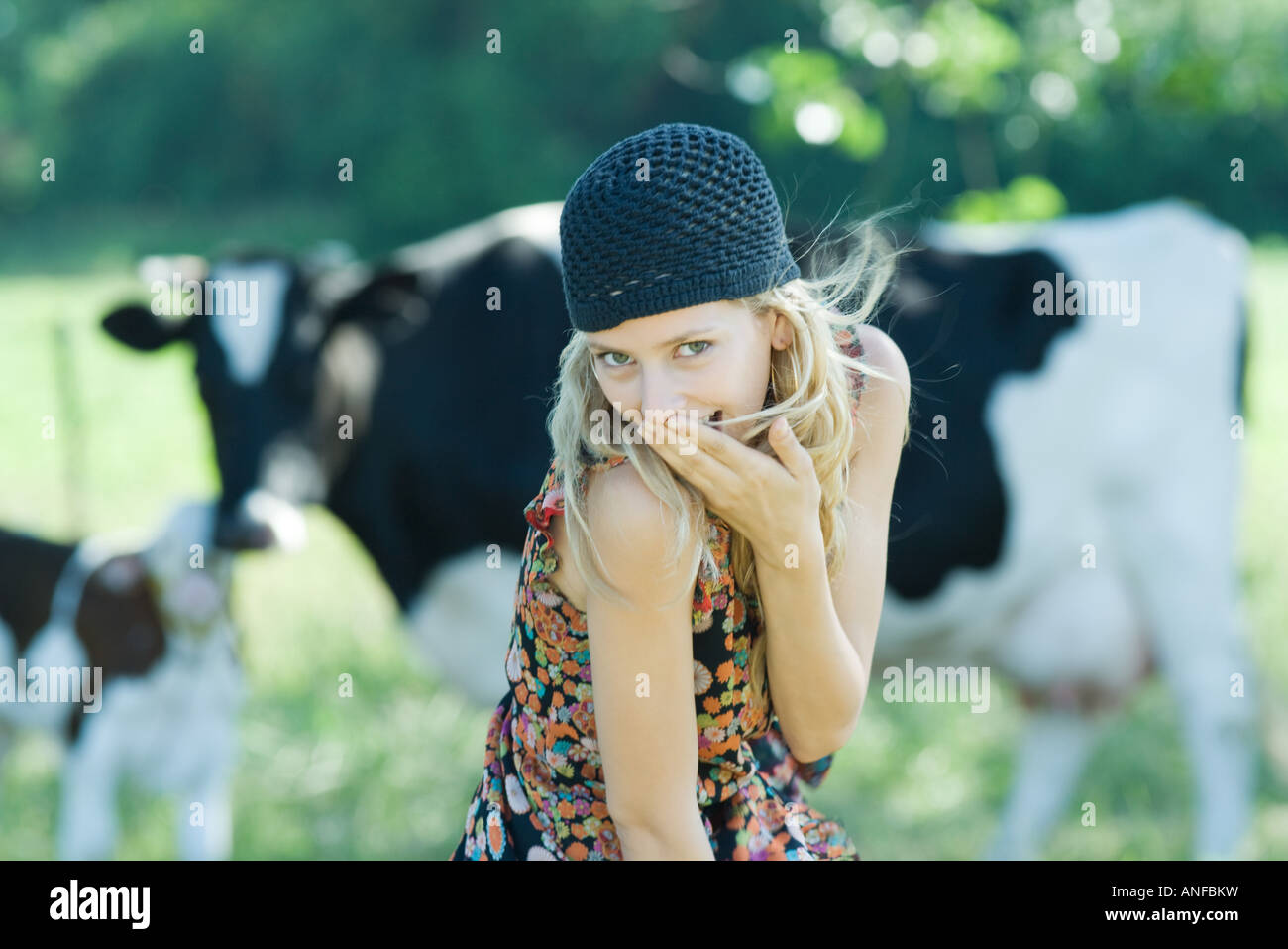 Young woman covering mouth with hand, looking at camera, cows in background - Stock Image