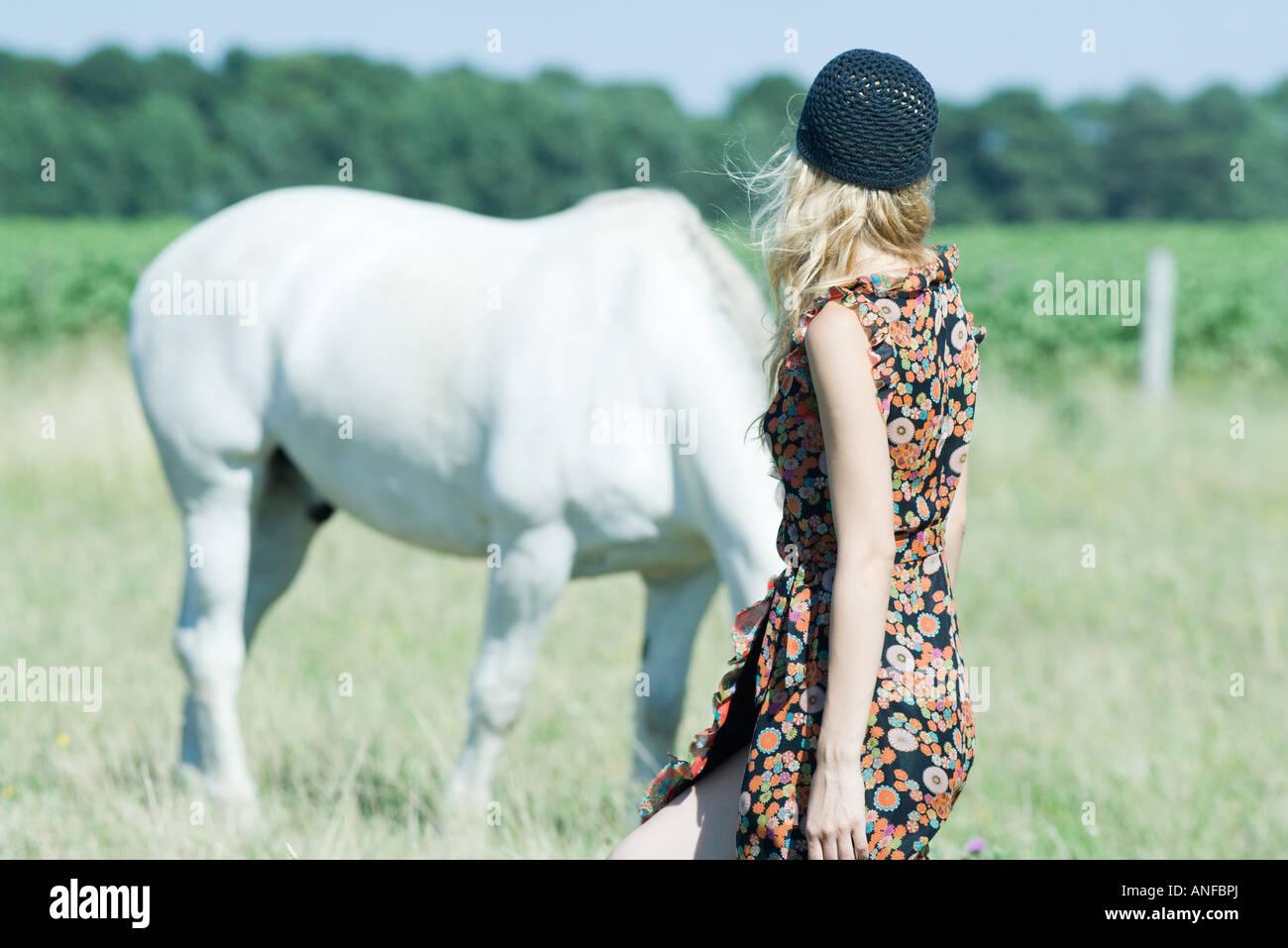 Young woman walking toward horse, rear view - Stock Image
