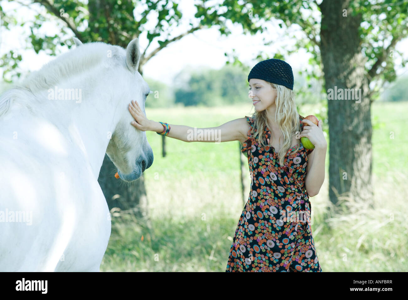 Young woman touching horse, holding apples - Stock Image