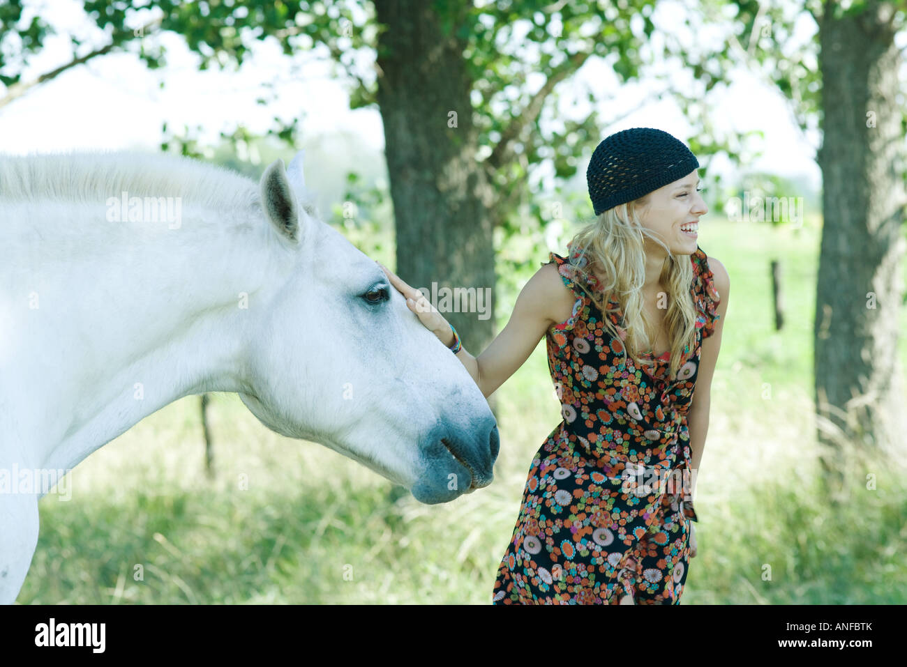 Young woman touching horse and laughing - Stock Image