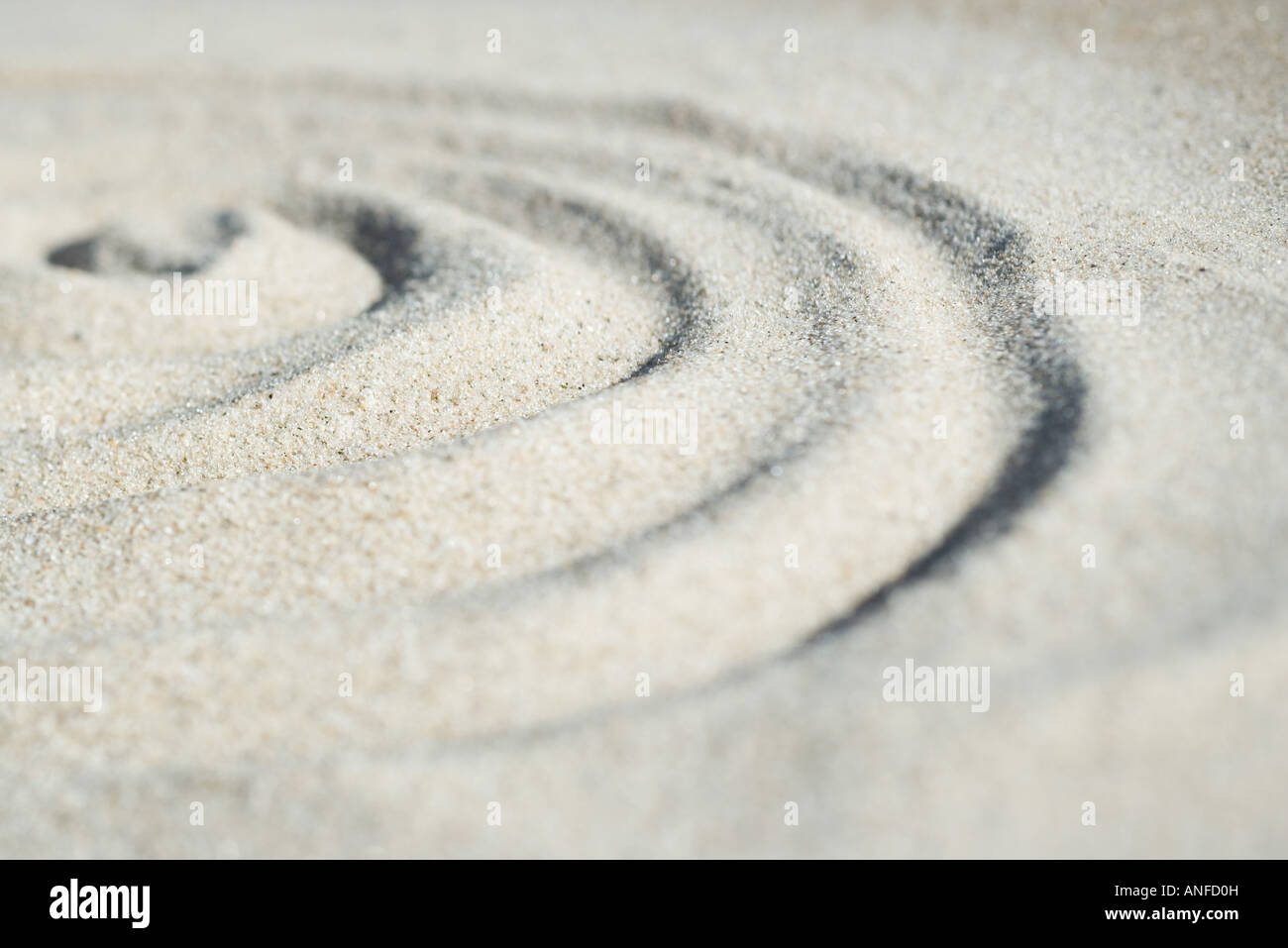 Spiral shape drawn in sand, close-up, surface level - Stock Image