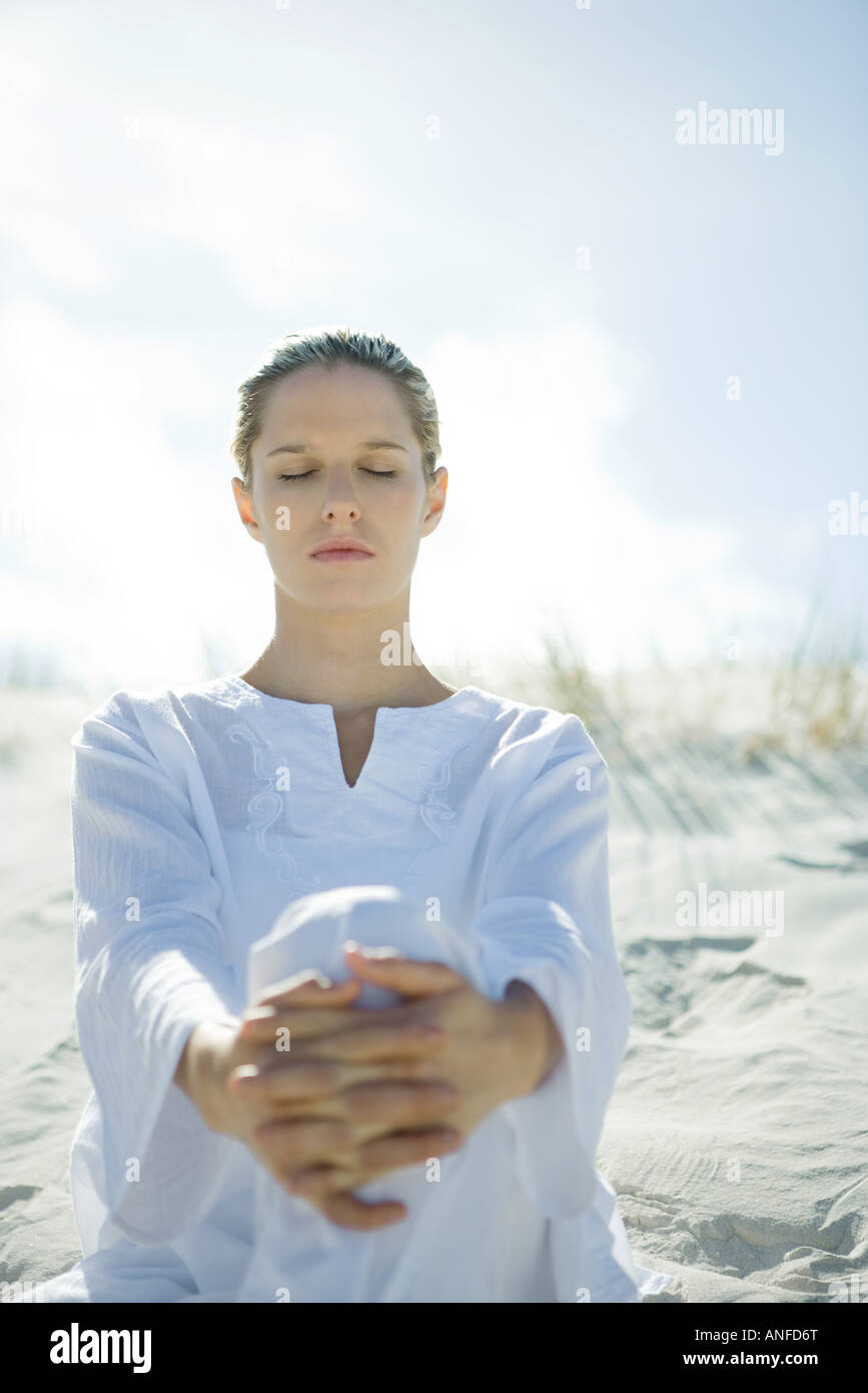 Young woman sitting on dune with eyes closed - Stock Image