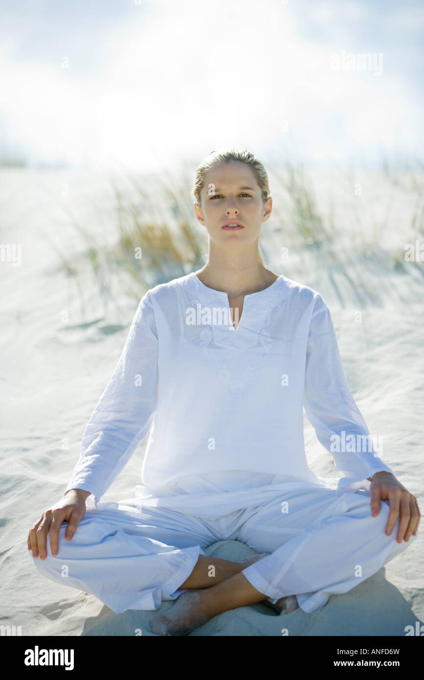 Young woman sitting on dunes, full length - Stock Image