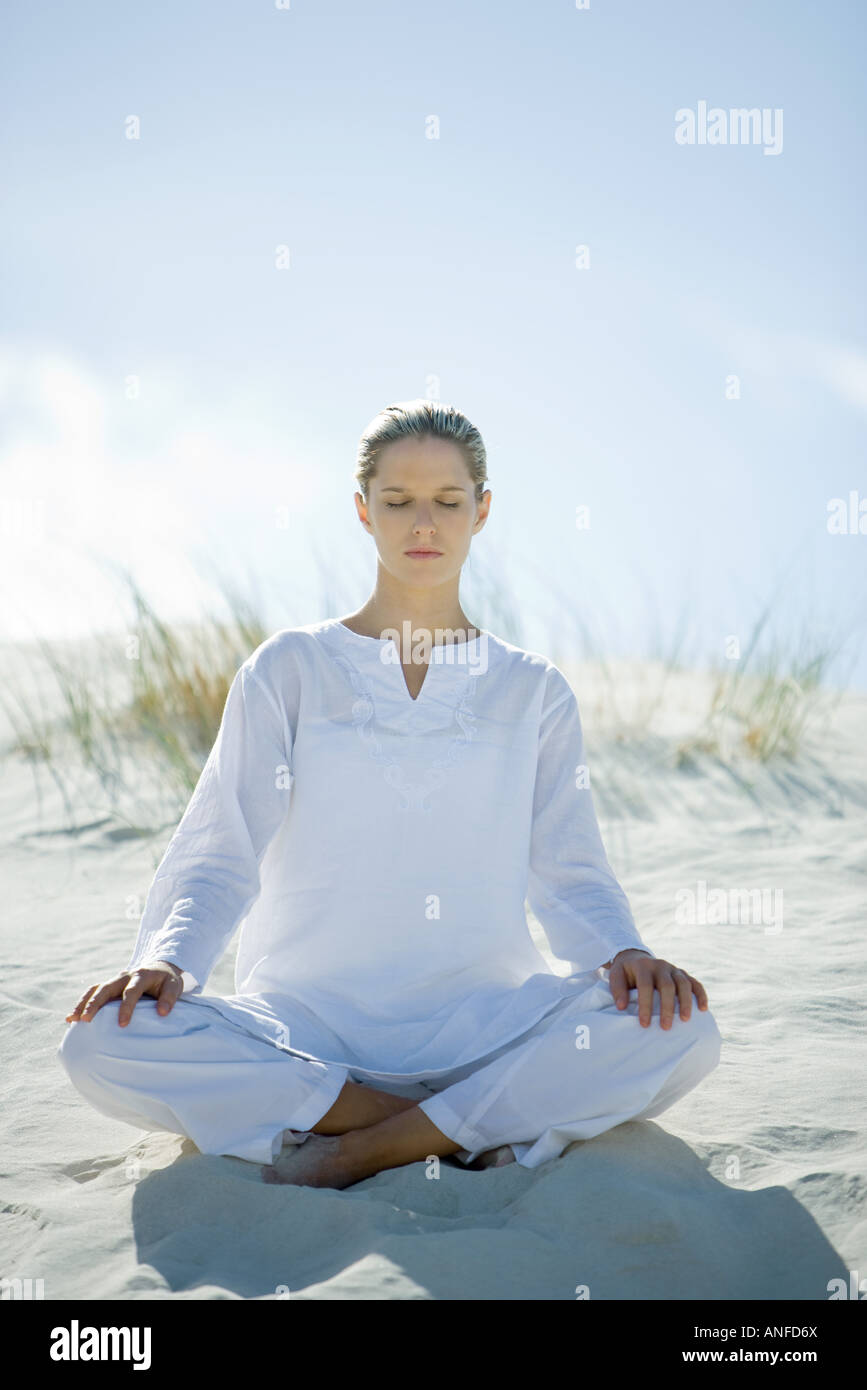 Young woman sitting on dune, eyes closed Stock Photo