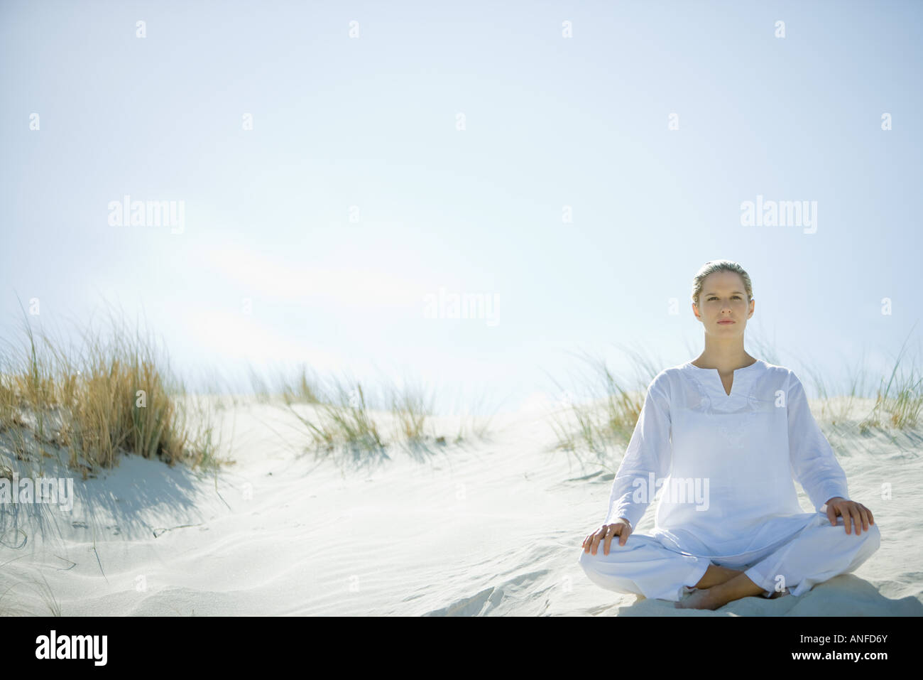 Young woman sitting on dune, full length - Stock Image