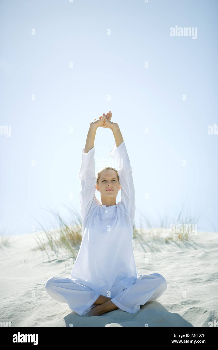 Young woman sitting on dune, stretching arms over head - Stock Image
