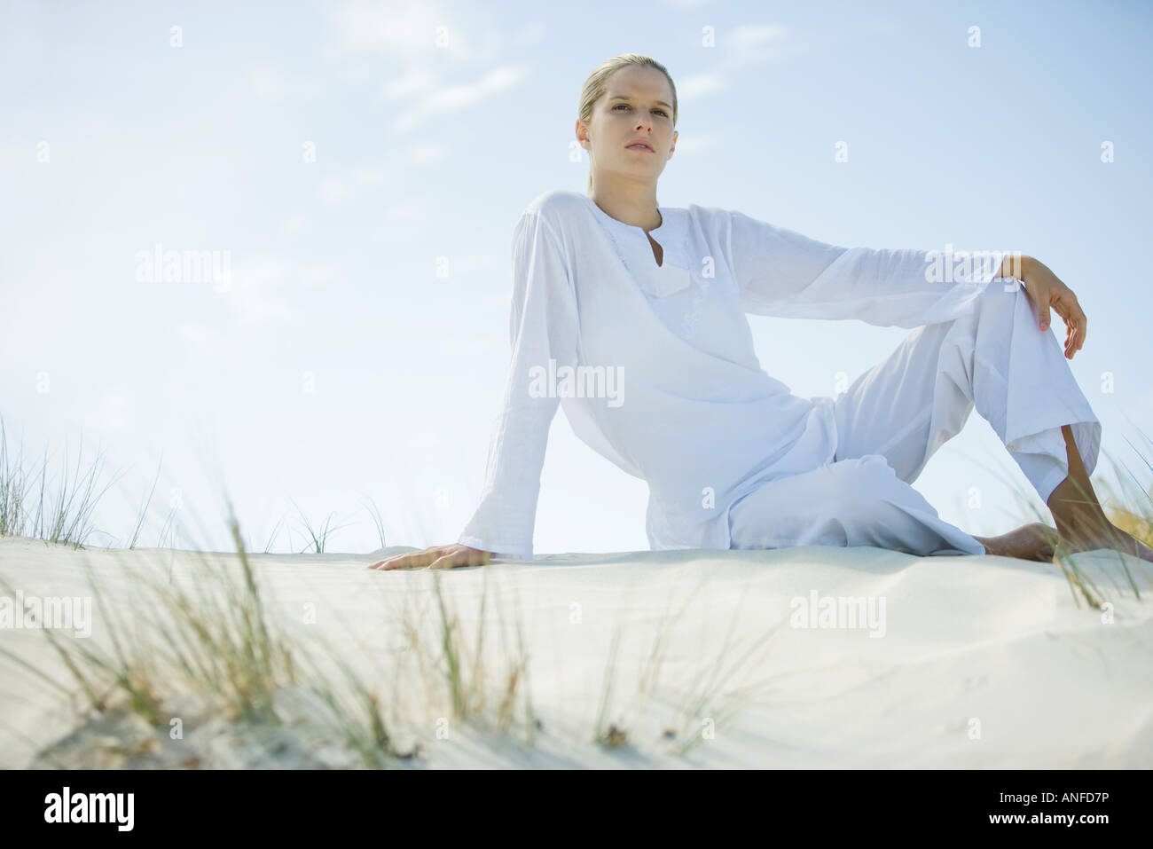 Young woman sitting on dune, low angle view - Stock Image