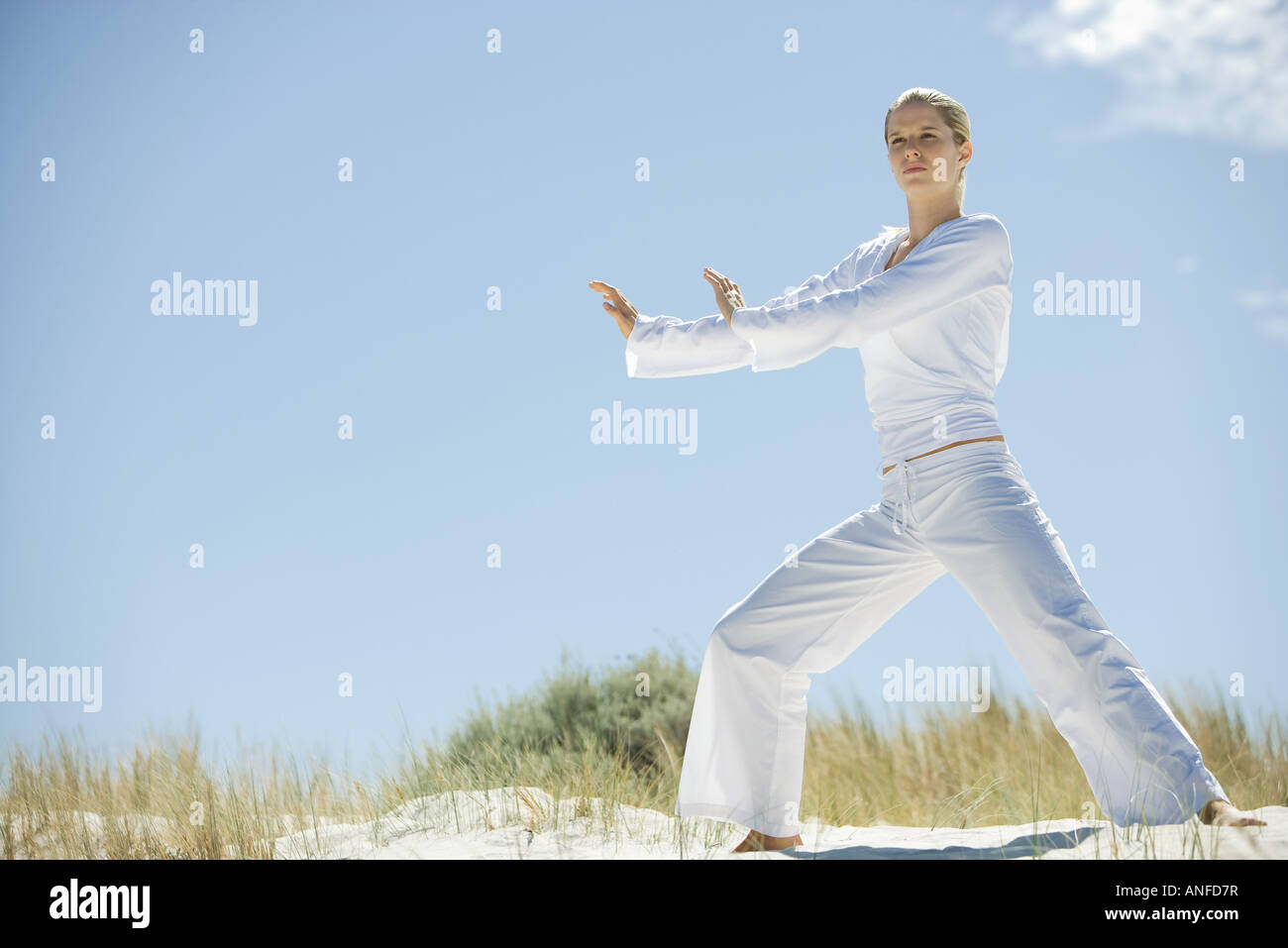 Young woman doing Tai Chi in dunes, full length - Stock Image