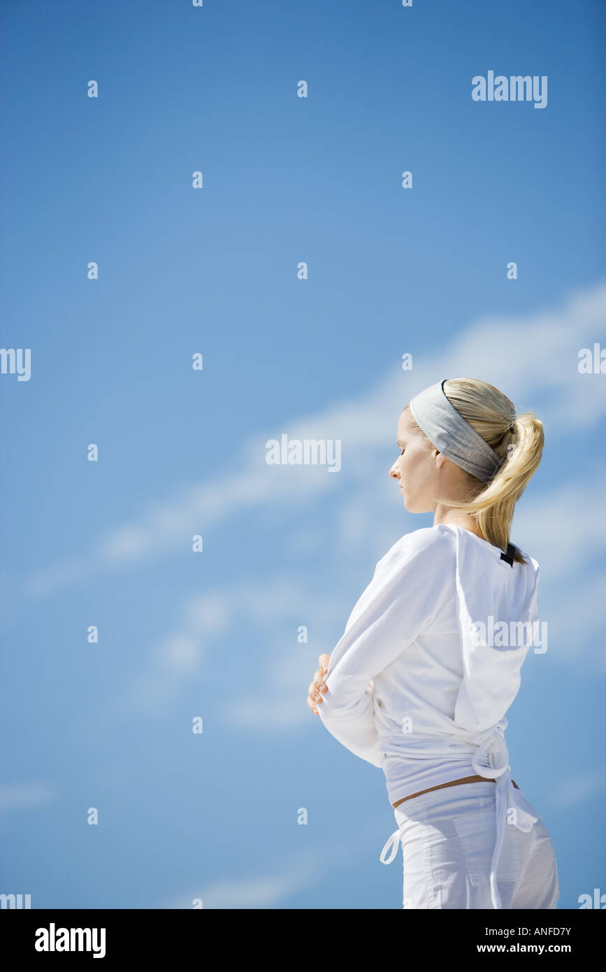Young woman standing with eyes closed and arms crossed, side view, sky in background - Stock Image