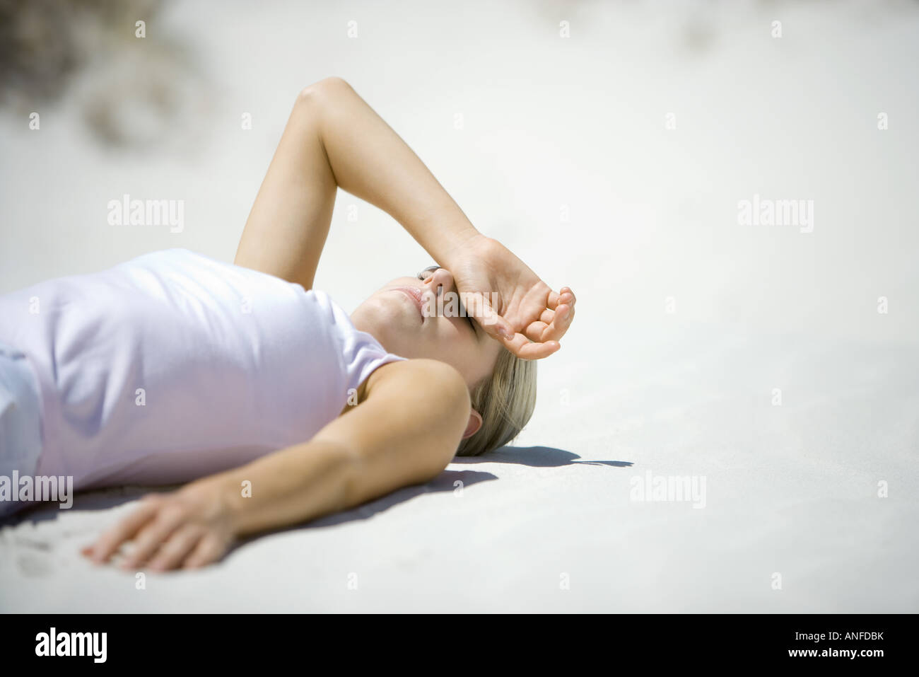 Young woman lying on beach, covering eyes with hand - Stock Image
