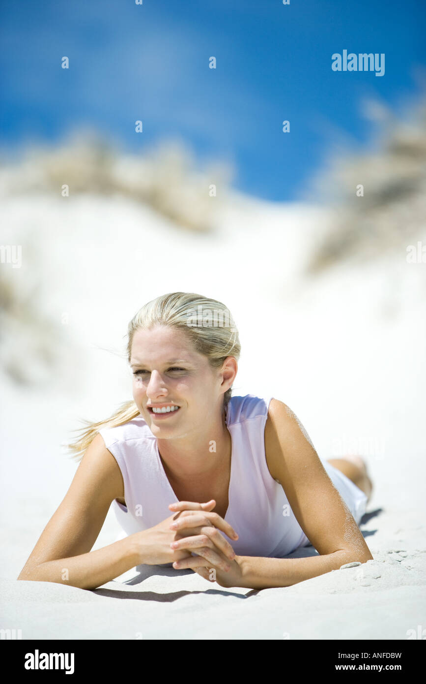 Young woman lying on beach, smiling - Stock Image