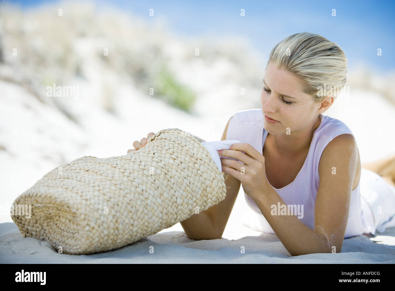 Young woman lying on beach, looking through beach bag - Stock Image