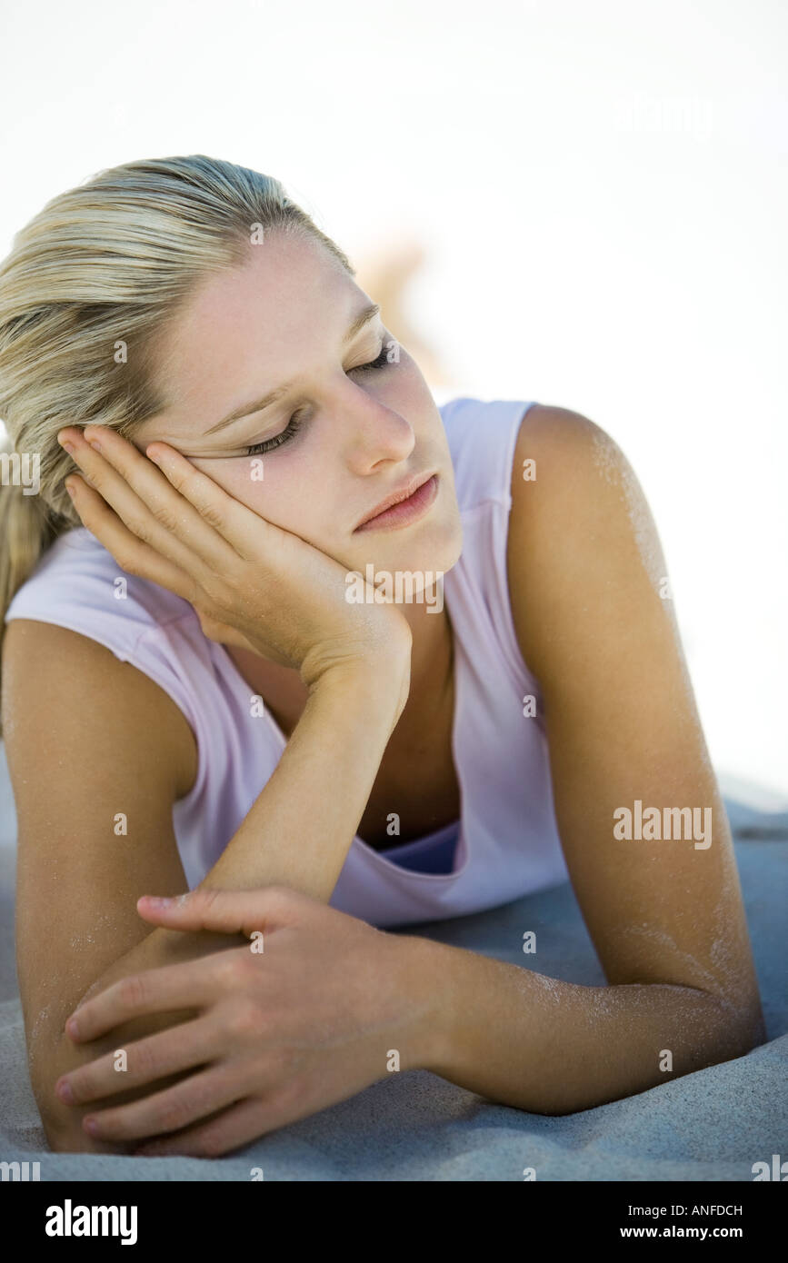 Young woman lying on sand, leaning on elbow, eyes closed - Stock Image