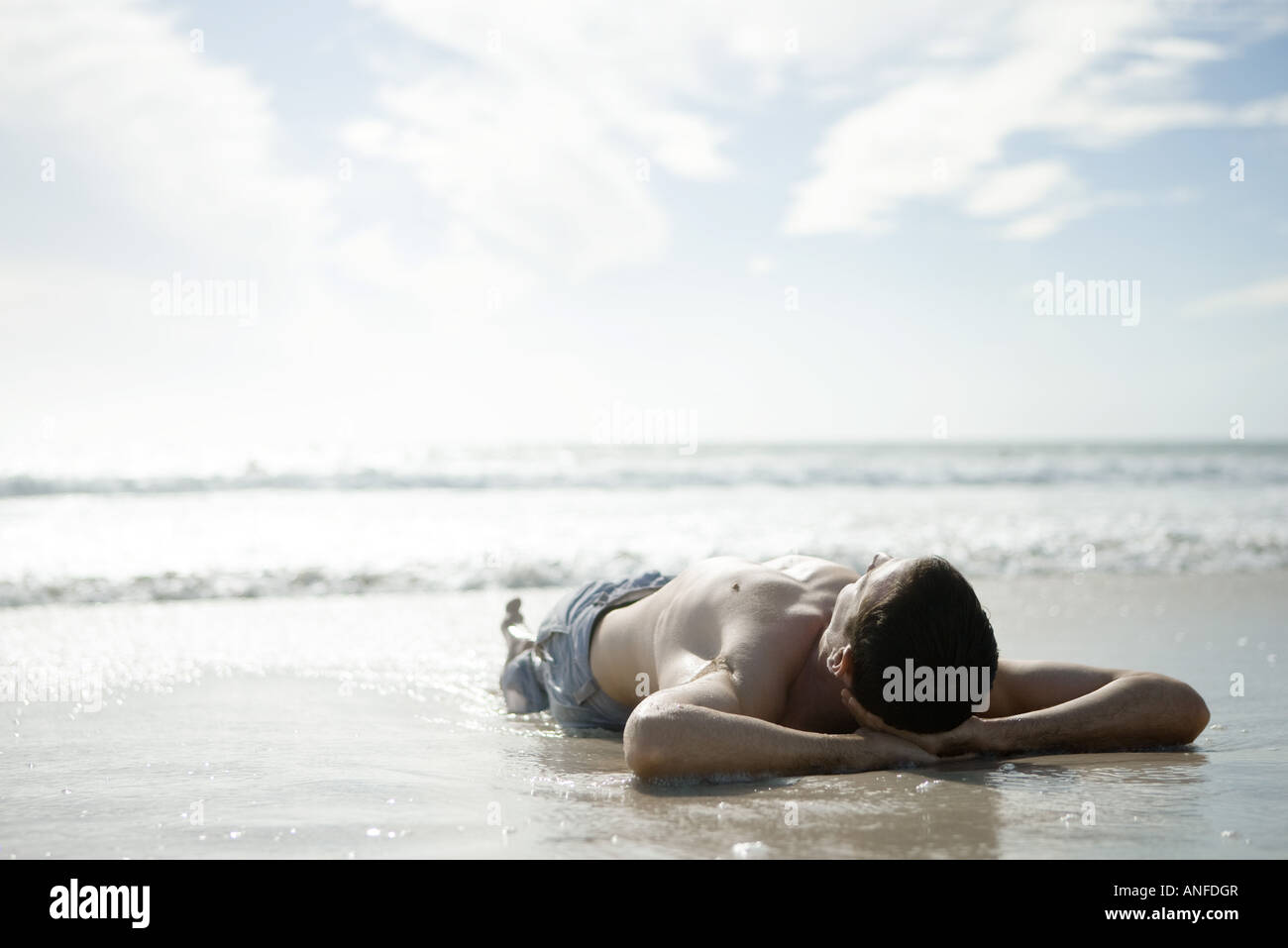 Young man lying on wet sand on beach, hands behind head - Stock Image