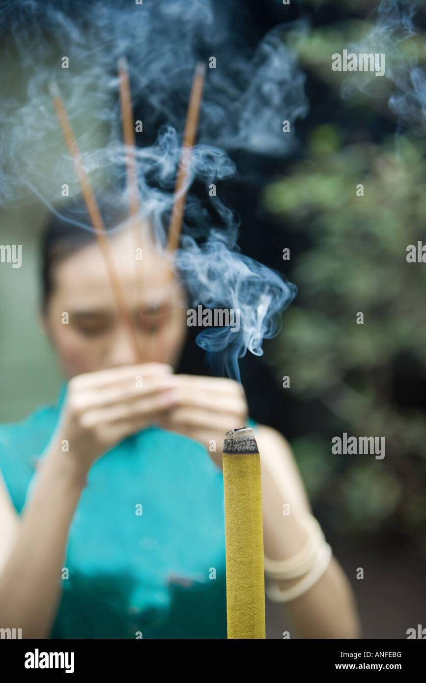 Young woman wearing traditional Chinese clothing, holding up incense - Stock Image