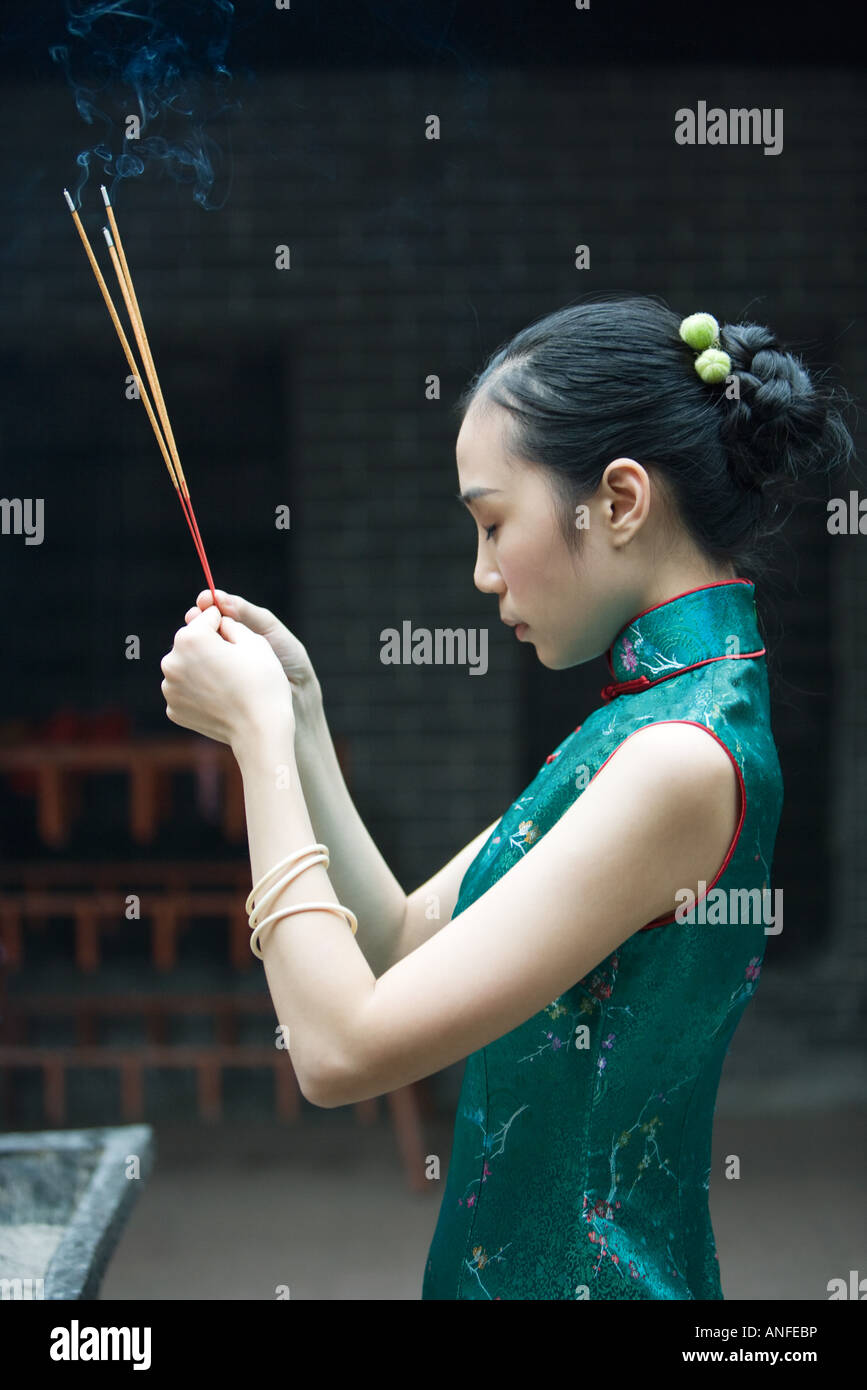 Young woman wearing traditional Chinese clothing, holding up incense, side view - Stock Image