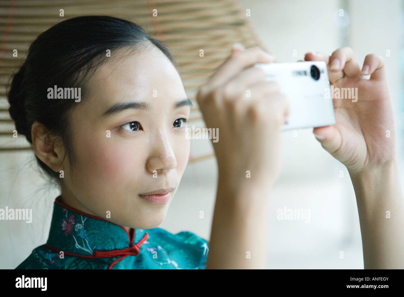 Young woman wearing traditional Chinese clothing, taking photo with digital camera - Stock Image