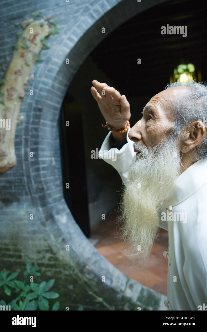 Elderly man wearing traditional Chinese clothing, looking up, side view - Stock Image