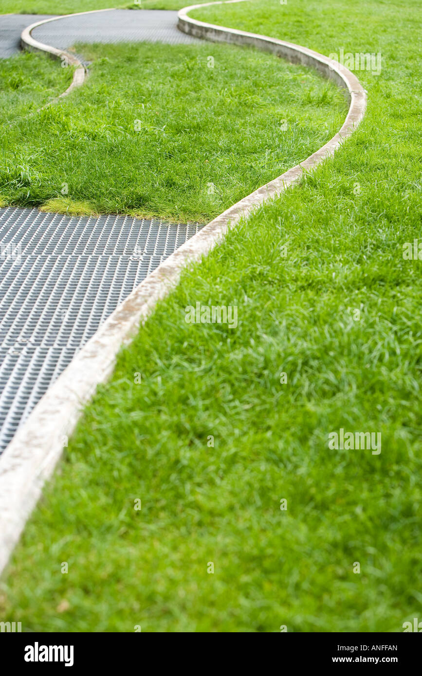 Metal grate and concrete curves in grass - Stock Image