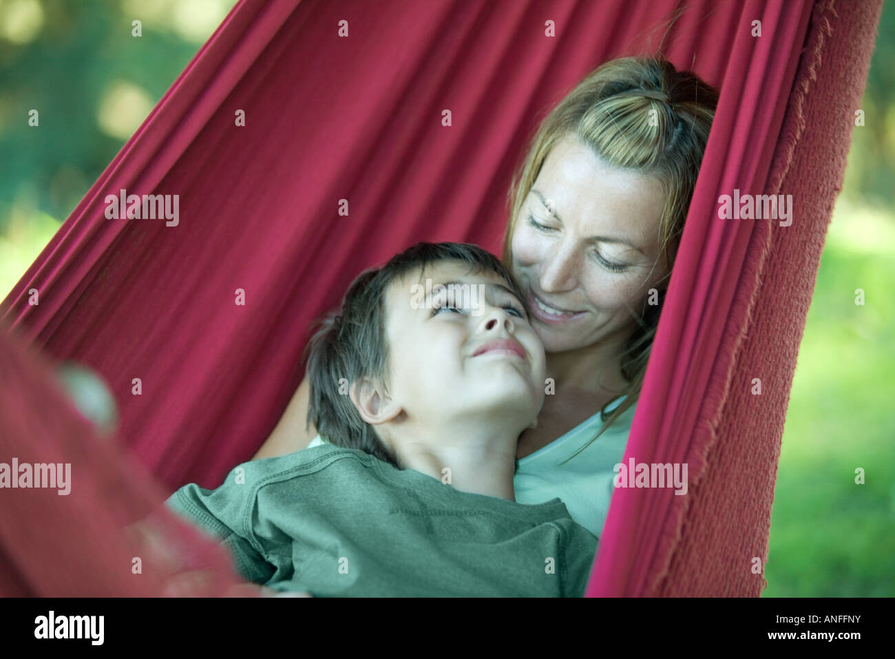 Boy and mother in hammock, smiling at each other - Stock Image