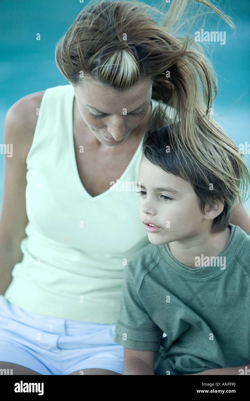 Boy and mother sitting in wind, portrait - Stock Image