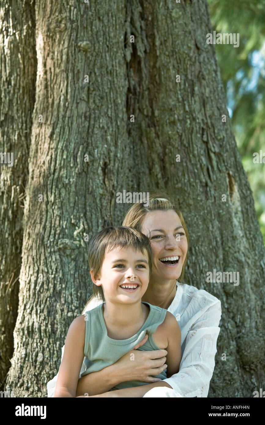 Mother and son, sitting at base of tree, laughing - Stock Image