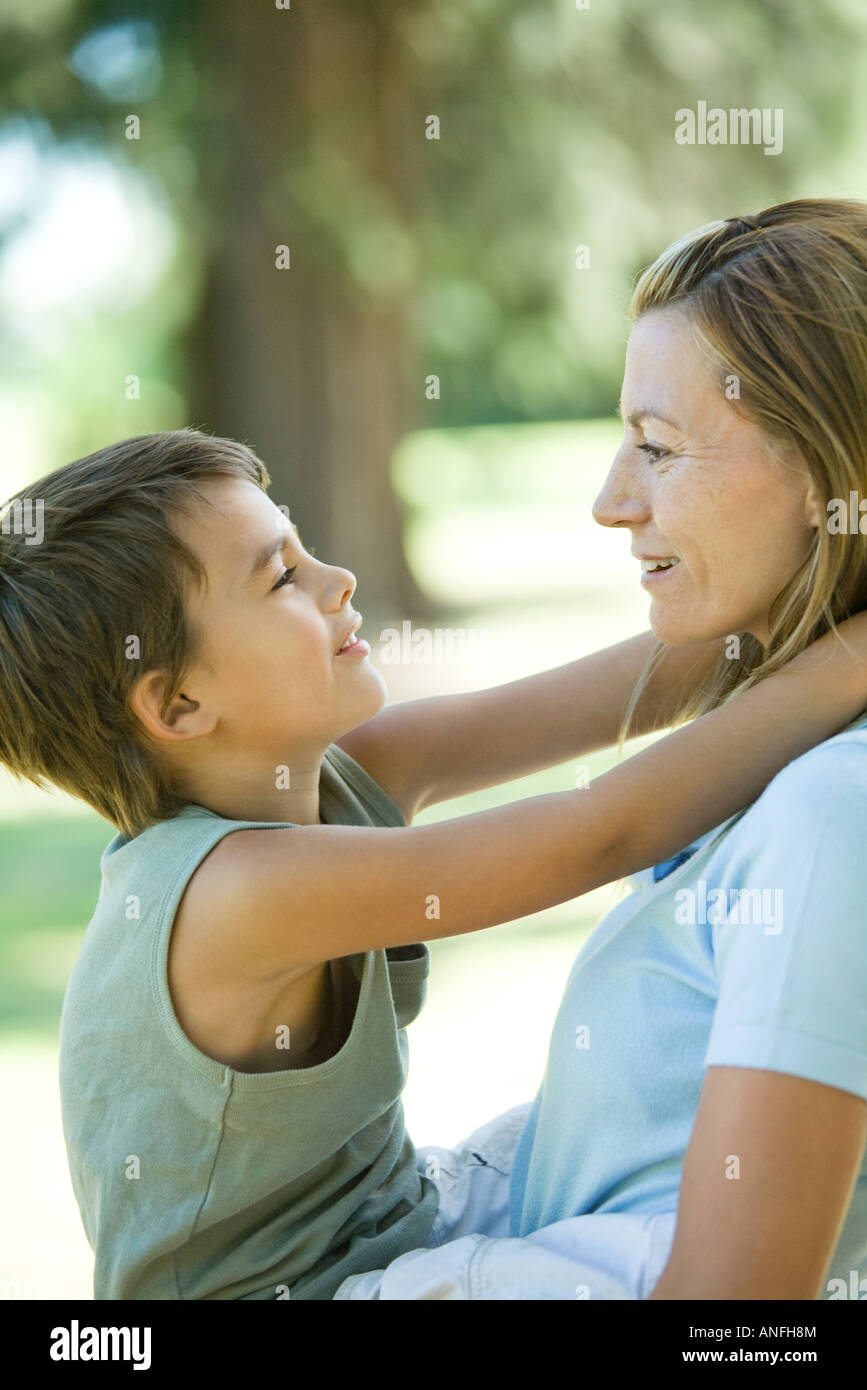 Mother holding son in arms, both smiling at each other, side view - Stock Image
