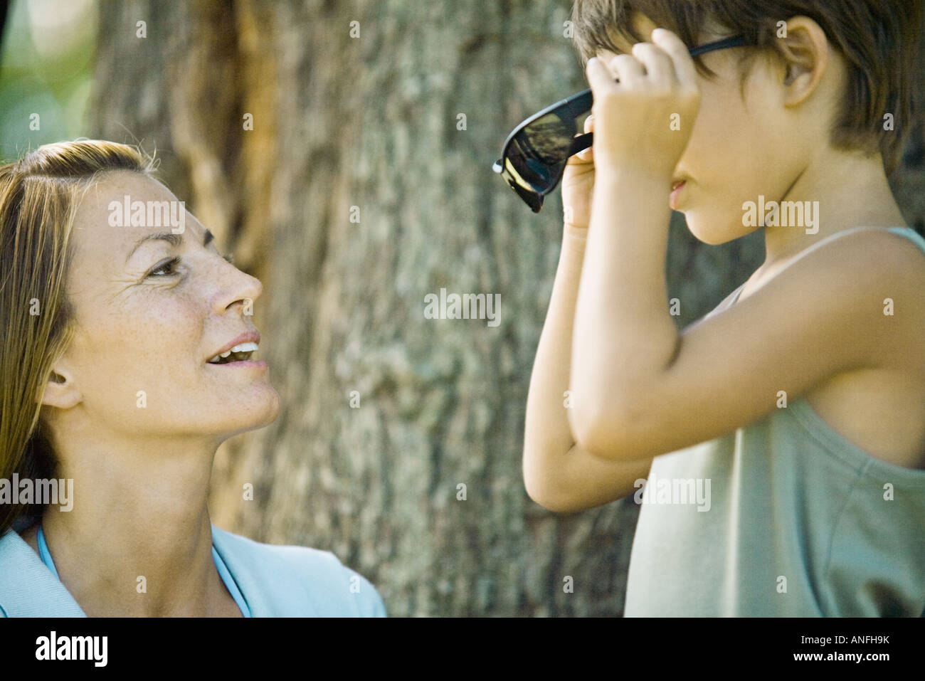 Mother and son, boy putting on sunglasses - Stock Image